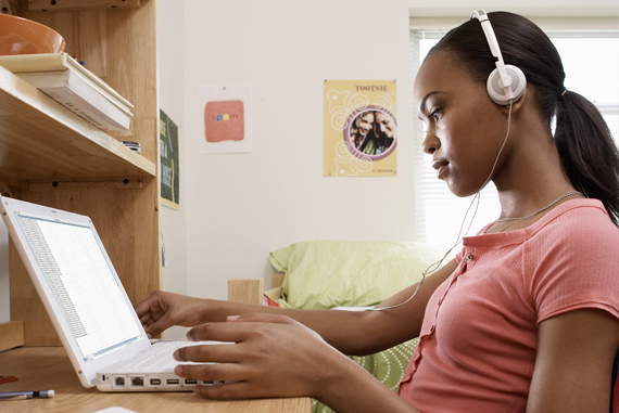 A female African-American student sits at a desk in her dorm room, wearing headphones and working on a laptop computer.
